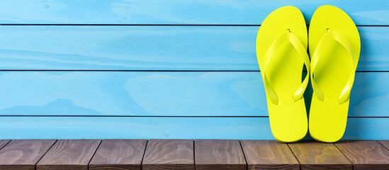 Green flip flops on wooden background. Close up