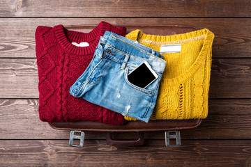 Female warm clothing for winter or autumn on top of vintage suitcase. Close up