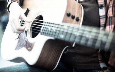 girl holding guitar. Focus on strings of guitar