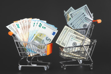 Two shopping carts with rival currencies, one filled with US dollar bills and another with Euro banknotes, conceptual picture.