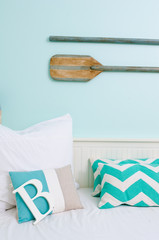 A rustic beach surf themed interior decorated room, with boat paddles and the letter B, in  a relaxing bohemian fresh setting.