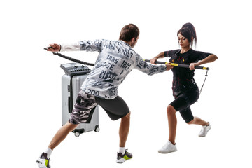 EMS fitness woman in full electrical muscular stimulation suit doing lunge exercise with a bar on flexible band. Trainer helps her. Studio shot isolated on white background.