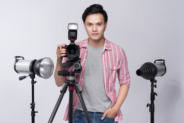 Young asian photographer holding digital camera, while working in studio