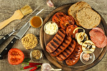 Grilled sausage with mustard on a wooden cutting board. Summer barbecue party. Fat meal.