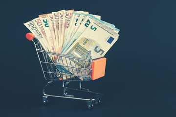 Shopping cart filled with Euro banknotes, color toning applied.