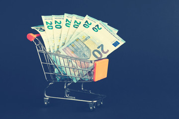 Shopping cart filled with one twenty Euro bills, color toning applied.