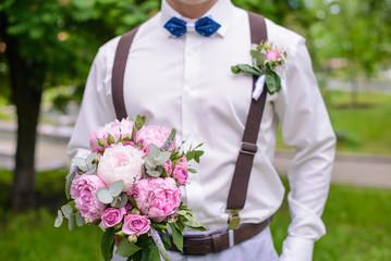 Wedding bouquet of peonies in hand the groom