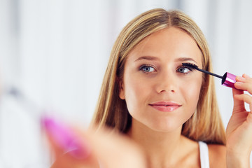 Beauty portrait of woman applying makeup and looking in the mirror. Painting eyelashes with mascara
