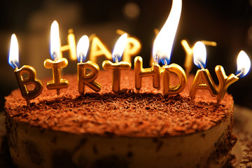 happy birthday candle with fire on a cake