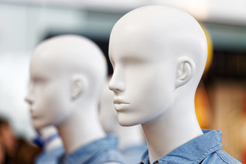 Closeup plastic mannequin heads against blurred background. Shallow focus.