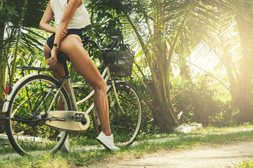 Sexy woman with bicycle at hot summer day
