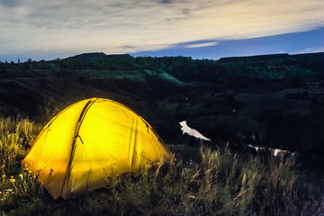 Illuminated yellow tent next to grand canyon at night in Krivoy Rog, Ukraine