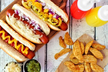 Hot dogs with assorted toppings and potato wedges, above view on a rustic white wood background