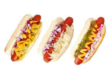Three hot dogs with an assortment of toppings, top view isolated on a white background