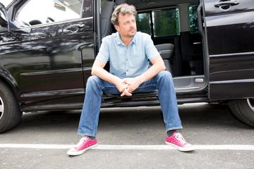 Portrait of a man siting his SUV van