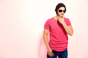 Hipster guy in sunglasses wearing brown hat and pink t-shirt touching chin holding hand in pocket.