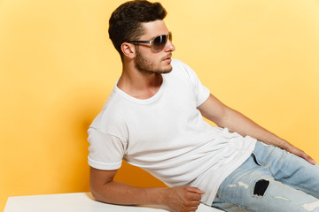 Good-looking young man in sunglasses wearing white t-shirt and jeans leaning upon white surface.
