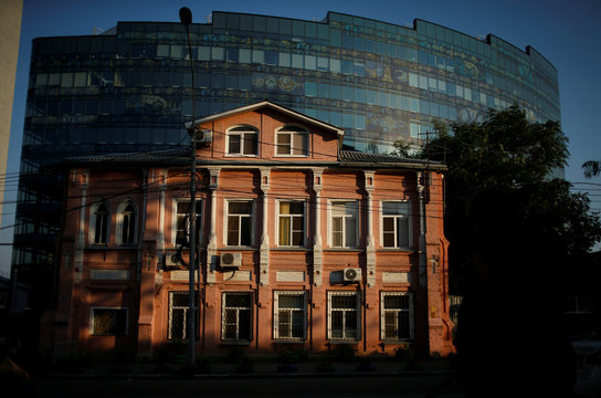 An old house is seen in front of a modern office building in Rostov-On-Don