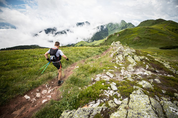 middle age male runner with backpack and poles on the mountain trail after rain with cloudy view