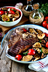 Grilled t-bone steak with grilled vegetables on an old wooden background. Rustic style.