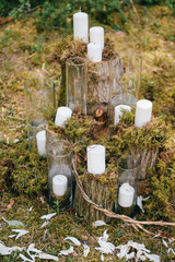 Wedding wooden arch for marriage ceremony with flowers, curtain and other decoration elements standing on ground in forest. Pine trees in sunny summer day. Celebration mood. Candles in glass, feathers