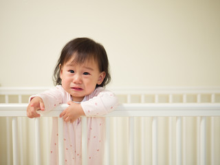 Baby girl crying in cot bed