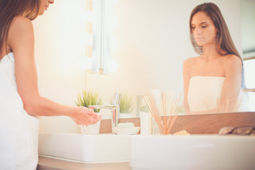 Young woman washing her face with clean water in bathroom