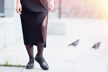 Woman in black pleated  dress, skirt with one knee open walking in the city streets. Fashion blogger concept. Toned