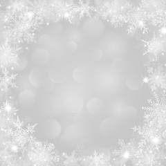 Christmas background with frame of snowflakes and bokeh effect in white