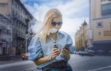 Blonde haired girl with vipe and cell phone in hands, on the background of city street. Day, outdoor