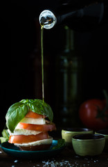 Caprese salad with olive oil pouring over