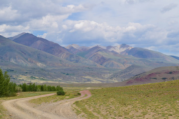 View of steppe and earth road in cloudy waether in Altai mountains. Altay Republic, Siberia, Russia.