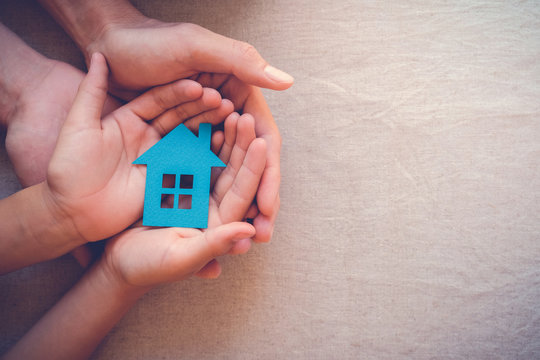 hands holding paper house, family home, homeless shelter, international day of families, foster home care, family day care, social distancing, stay at home, mortgage housing crisis  concept