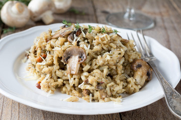 Mushroom risotto on white plate on wooden table. Closeup view