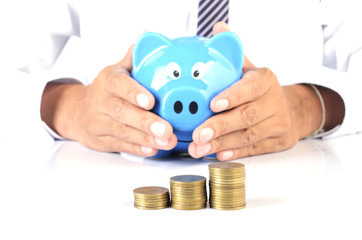 close up of money coins stack and business man keep blue piggy bank for financial ideas concept backgrounds
