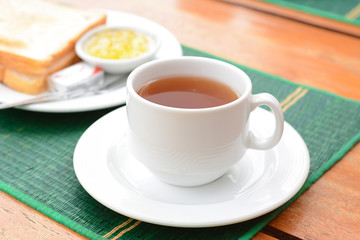 Hot tea in white cup with sliced bread on green mat