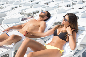 young couple on pool chairs
