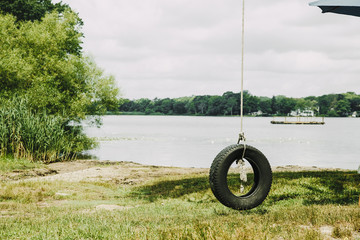 old tire swing hanged on a tree. summer swing hanging near the river. retro style