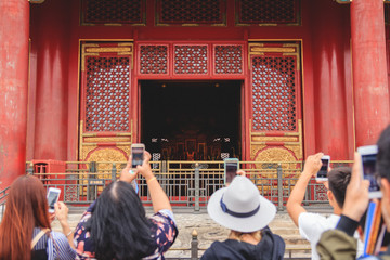Group of tourists taking pictures of a monument in The Forbidden City in Beijing, China