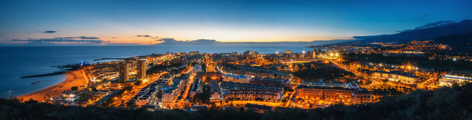 Panoramic view of the Illuminated Las Americas at night against the colorful sunset sky with lights on the horizon on Tenerife island, Spain