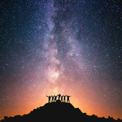 Together we stand. A group of people are standing on the top of the hill next to the Milky Way galaxy holding hands.