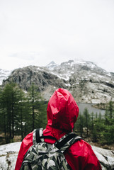 Hiking girl in the mountains relaxing in front to a silent lake in italy - Aosta