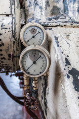 two factory gauges in front of peeling paint