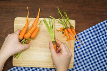 Top view close-up young woman hands Cook with carrots on the wooden table.