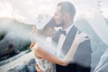Groom hugs bride tender standing on the rock