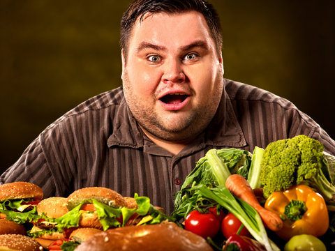 Fat man who makes choice between healthy and unhealthy food. Overweight male with hamburgers, french fries and vegetables trays trying to lose weight first time. Poor food leads to obesity.