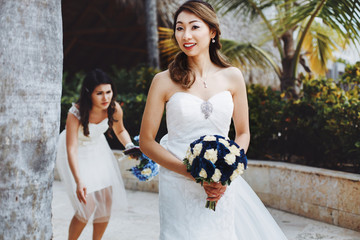 Stunning bride with blue bouquet walks on the backyard