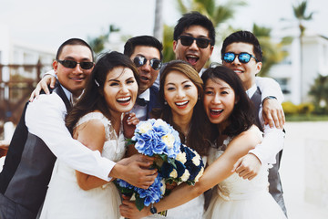 Warm hugs of newlyweds and friends having fun while they pose outside