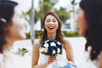 Laughing bride stands outside with cheerful bridesmaids