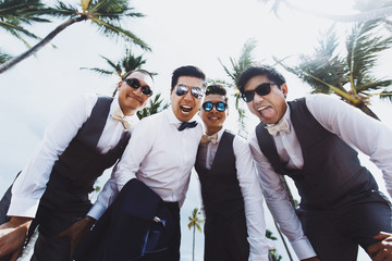 Stylish groom and groomsmen pose under tall green palms